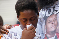 Cal Brown, held by husband Michael Brown Sr., sheds a tear at the spot where his son was killed comforts during 4 1/2 minutes of silence to mark the one year anniversary of the killing of son Michael Brown Jr. in Ferguson, Missouri August 9, 2015.  Several hundred people gathered in Ferguson, Missouri, on Sunday to mark the one-year anniversary of the shooting death of an unarmed black teenager by a white police officer that sparked protests and a national debate on race and justice.  Brown's shirt (R) bears the image of Michael Brown Jr. REUTERS/Rick Wilking