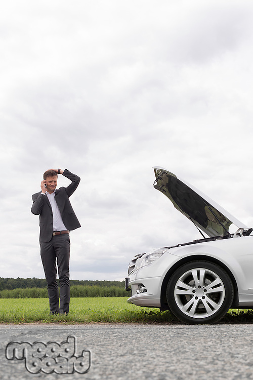 Frustrated young businessman using cell phone near broken down car at countryside