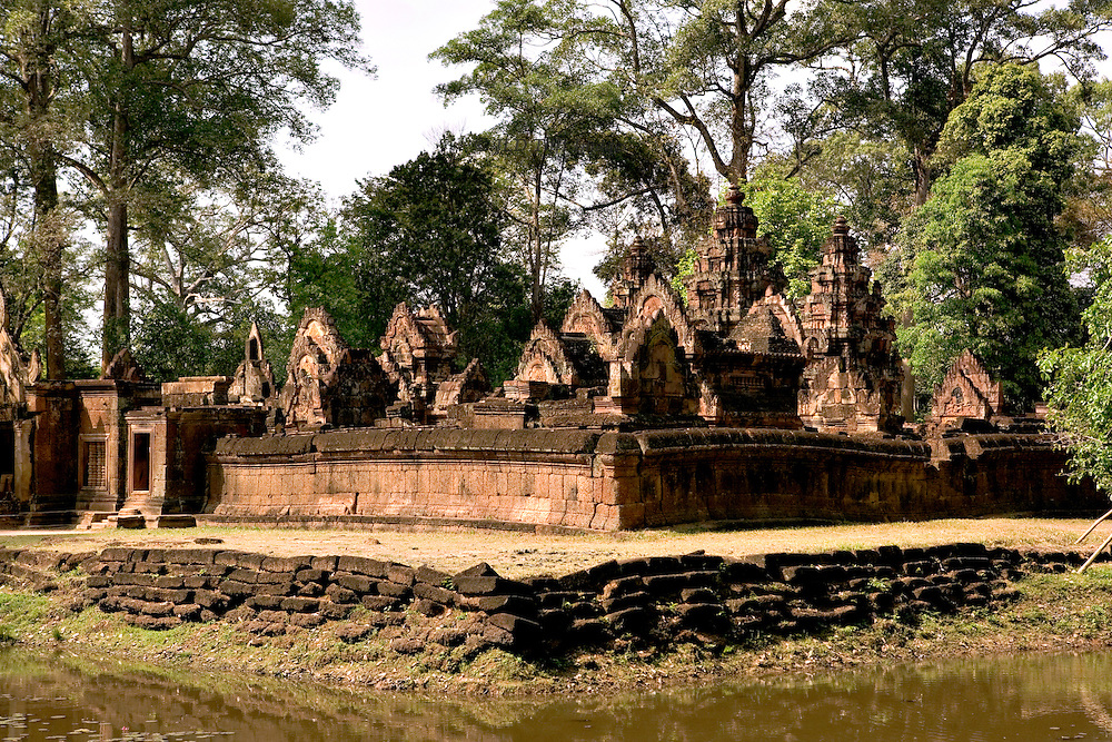 Angkor . Banteay Srei temple enclosure and moat, showing central towers.  Three quarter view from across its moat.
