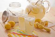 Two glasses of fresh squeezed lemonade with pitcher of lemonade fresh lemons,sugar jar,colorful straws on light wooden table,bright window light,morning fresh look