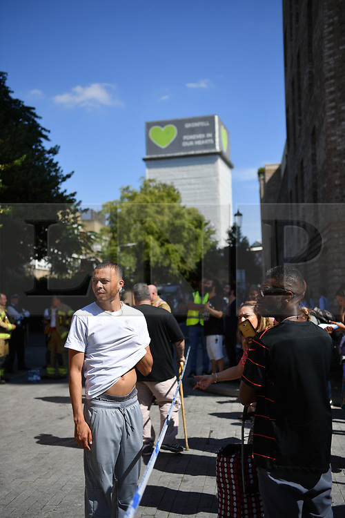 © Licensed to London News Pictures. 23/08/2019. London, UK.  Evacuated residents, Grenfell Tower in background. A fire broke out on the 12th floor of a tower block very close to the devastating inferno that destroyed Grenfell Tower killing 72 people two years ago. Ten engines and 70 firefighters brought the blaze under control which gutted the apartment and spread externally along satellite cables. Residents of Markland House self evacuated and commented that no fire alarms were heard in the building.  Photo credit: Guilhem Baker/LNP