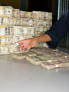 Federal Reserve worker counts and stacks bundles of U.S. cash.
