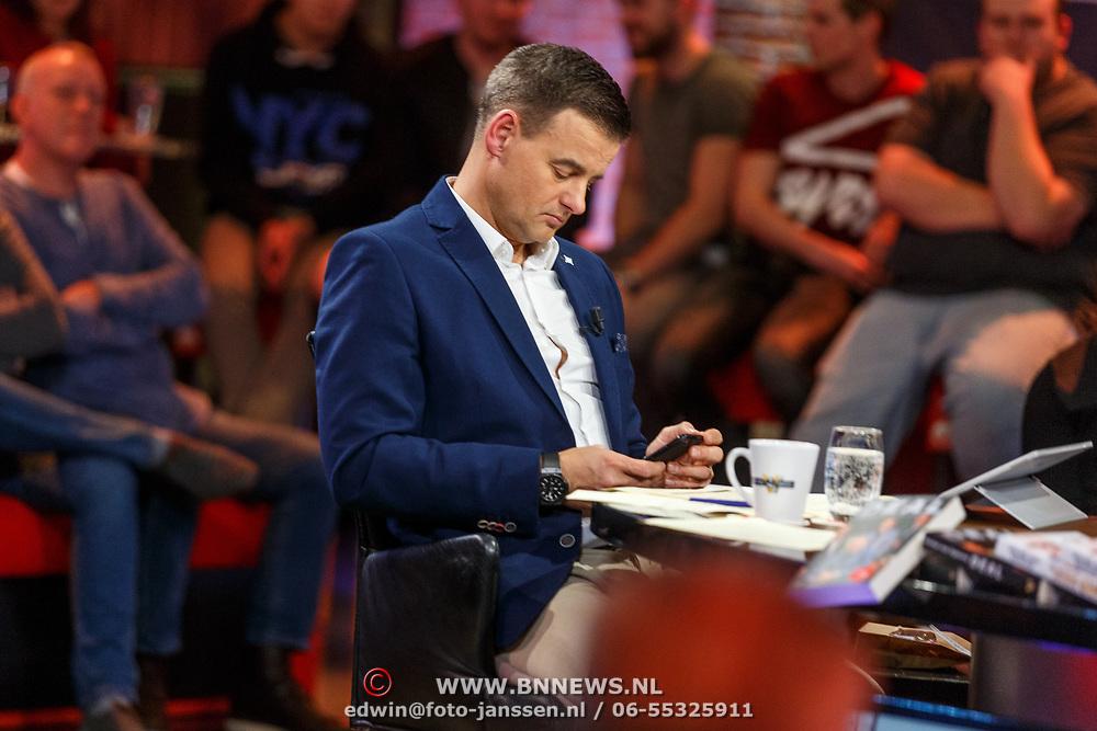 NLD/Hilversum/20171215 - Dick Advocaat te gast bij Voetbal Inside, presentator Wilfred Genee kijkt op zijn telefoon