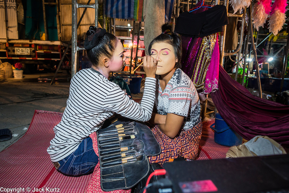 19 JANUARY 2014 - BANGKOK, THAILAND:  Performers in a mor lam show puts on makeup before going on stage at a mor lam show in Khlong Tan Market in Bangkok. Mor Lam is a traditional Lao form of song in Laos and Isan (northeast Thailand). It is sometimes compared to American country music, song usually revolve around unrequited love, mor lam and the complexities of rural life. Mor Lam shows are an important part of festivals and fairs in rural Thailand. Mor lam has become very popular in Isan migrant communities in Bangkok. Once performed by bands and singers, live performances are now spectacles, involving several singers, a dance troupe and comedians. The dancers (or hang khreuang) in particular often wear fancy costumes, and singers go through several costume changes in the course of a performance. Prathom Bunteung Silp is one of the best known Mor Lam troupes in Thailand with more than 250 performers and a total crew of almost 300 people. The troupe has been performing for more 55 years. It forms every August and performs through June then breaks for the rainy season.              PHOTO BY JACK KURTZ