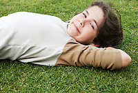 Pre-teen boy lying on back in grass hands behind head ground view