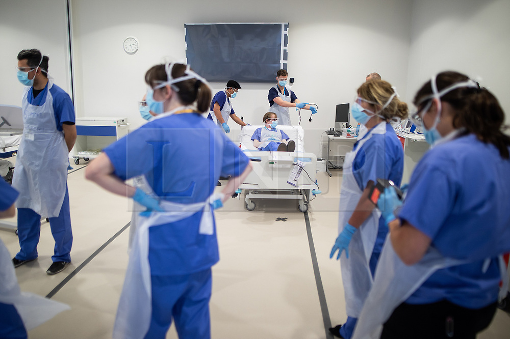 © Licensed to London News Pictures . 15/04/2020. Manchester, UK. Clinicians wearing PPE role play treating a patient in cardiac arrest (played by a ward nurse) in the dedicated resuscitation room of the Nightingale NW Hospital . The National Health Service has built a 648 bed field hospital for the treatment of Covid-19 patients , at the historical railway station terminus which now forms the main hall of the Manchester Central Convention Centre . The facility is due to fully open this week (ending Friday 17th April 2020 ) and will treat patients from across the North West of England , providing them with general medical care and oxygen therapy after discharge from Intensive Care Units . Photo credit : Joel Goodman/LNP