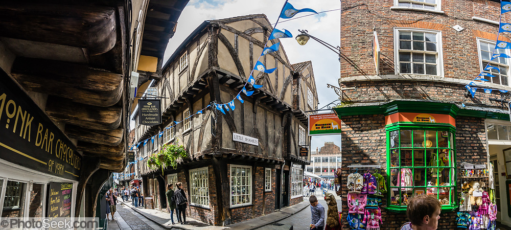 "The charming Shambles is one of the best preserved medieval streets in the world, and sits amid a district of twisting, narrow streets in York, England, United Kingdom, Europe. The Shambles was mentioned in the Doomsday Book of William the Conqueror in 1086. Many of its buildings date from 1350-1475, when the street hosted butchers' shops and houses. The overhanging timber-framed fronts of the Tudor buildings shelter the ""wattle and daub"" walls below and would keep direct sunshine off of the butchers' meat. ""Shambles"" may derive from ""Shammel,"" an Anglo-Saxon word for the slaughterhouse shelves of the open shop-fronts. This image was stitched from multiple overlapping photos."
