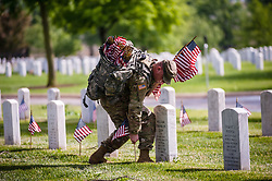 May 23, 2019 - Arlington, VA, United States - Soldiers assigned to the 3d U.S. Infantry Regiment (The Old Guard) place US flags on graves at Arlington National Cemetery on May 24, 2018 ahead of Memorial Day in Arlington, Virginia. (Credit Image: © Michael A. McCoy/ZUMA Wire)