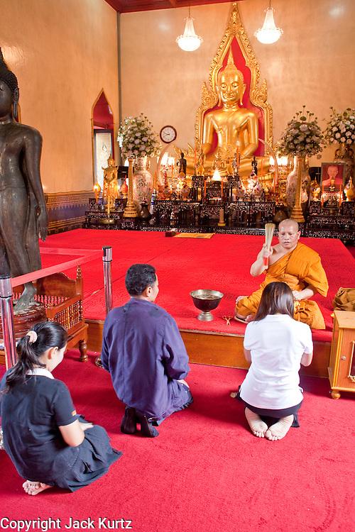 07 OCTOBER 2009 -- BANGKOK, THAILAND:  A Buddhist monk hears people's prayers in Wat Traimit (Temple of the Golden Buddha) in Bangkok, Thailand.   Photo By Jack Kurtz