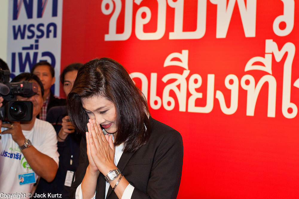 """03 JULY 2011 - BANGKOK, THAILAND:     YINGLUCK SHINAWATRA, the Prime Minister elect of Thailand, performs a """"wai"""" or traditional Thai greeting before announcing her victory in the Thai elections Sunday night. If her election holds she will be the first woman elected Prime Minister of Thailand. Yingluck Shinawatra and the Pheu Thai Party scored a massive landslide win in the Thai election Sunday. Pheu That is estimated to have won more than 300 seats in Thailand 500 seat parliament, so they won an absolute majority and could govern without having to form a coalition with minor parties. Pheu Thai is the latest incarnation of deposed former Prime Minister Thaksin Shinawatra's political party. Yingluck is his youngest sister. Many observers expect legal challenges to the Pheu Thai victory and the election does not completely resolve Thailand's difficult political history of the last five years.  PHOTO BY JACK KURTZ"""