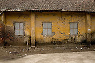 Facade of a house falling into disrepair. Yellow wall starts to be covered of moss and shutters are closed. Vietnam, Asia