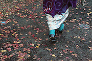 woman dressed in kimono walking over pavement with autumn leaves Japan
