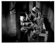 """Young Burmese woman applies """"thanaka"""" sun screen/make up, make from the bark of a tree, to her face in her room, Bagan, Burma."""