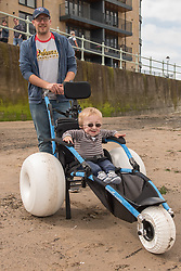 The Commonwealth Games Queen's Baton came to Portobello Beach and it still wasn't the biggest thing happening there. The Big Beach Busk, now in its eighth year was just getting underway when the Baton arrived at the beach volleyball courts by Portobello Baths where a Men's CEV Continental Tour competition was underway. Pictured: Ethan Brown is delight to try out the new Beach Wheelchairs now avialble for wheelchair users to get down onto the sand at Portobello. The chairs are available from beside Tumbles.<br /> <br /> <br /> © Jon Davey/ EEm