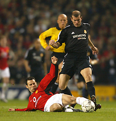 MANCHESTER, ENGLAND - Wednesday, April 23, 2003: Real Madrid's Zinadine Zidane skips past the challenge of Manchester United's Ryan Giggs during the UEFA Champions League Quarter Final 2nd Leg match at Old Trafford. (Pic by David Rawcliffe/Propaganda)