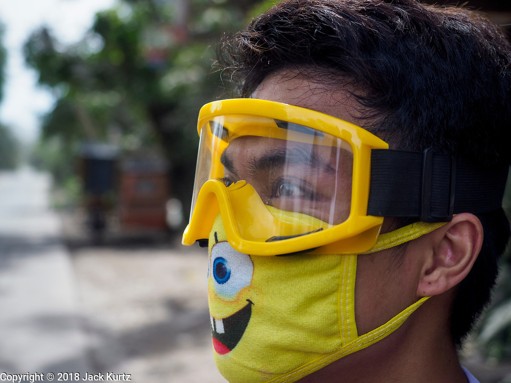 30 JANUARY 2018 - GUINOBATAN, ALBAY, PHILIPPINES: A man wearing a face mask and goggles for protection watches Mayon volcano during an ash fall in Guinobatan. Mayon volcano continued to erupt but not as dramatically as it did last week. The small eruptions are still sending ash clouds over communities west of the volcano and the government is encouraging people to stay indoors, wear face masks and avoid strenuous activities when ash is falling.     PHOTO BY JACK KURTZ
