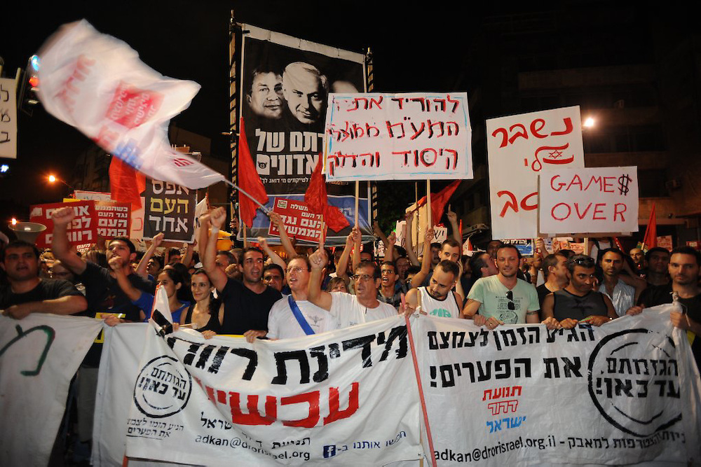 TEL AVIV, ISRAEL - JULY 30, 2011: Thousands of Israeli marched in Tel Aviv against the soaring cost of living. Israeli all over Israel attended protests against the living costs on July 30, 2011. Some hundreds of protesters blocked a main road in Tel-Aviv and cofronted with police. Several protesters were arrested.