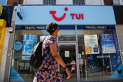 © Licensed to London News Pictures. 30/07/2020. London, UK. A woman wearing a face covering walks past a Tui store on Wood Green High Road in north London. Tour operator Tui announced that 166 high street stores in the UK and the Republic of Ireland will shut due to a downturn in travel caused by the coronavirus pandemic. Photo credit: Dinendra Haria/LNP