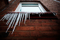 Icicles hanging from the window of a Victorian terraced house in Bearwood, Birmingham, England, UK.