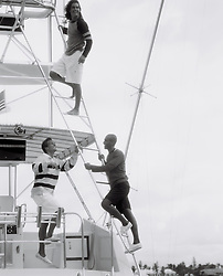 Man climbing the rigging of a Yacht