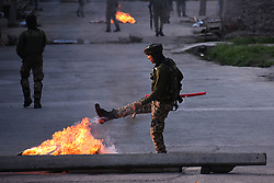 May 26, 2019 - Srinagar, Kashmir, India - An Indian paramilitary soldier kicks the burning tyre placed by protesters in Srinagar,Kashmir on May 25, 2019.Anti India clashes erupt in many area of Srinagar soon after Indian forces left curfew hit areas.Police used tear gas canisters to disperse the angry protesters.Earlier the resistance leader Syed Ali Shah Geelani had called for shutdown in Kashmir against the killing of militant commander Zakir Musa who headed the Al-Qaeda affiliate Ansar Gazwatul Hind.Zakir was killed by Indian forces during a fierce gun-battle in south Kashmir's Dadsara area of Tral. (Credit Image: © Faisal Khan/NurPhoto via ZUMA Press)