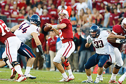 November 6, 2010; Stanford, CA, USA;  Stanford Cardinal quarterback Andrew Luck (12) is pressured by Arizona Wildcats defensive end Ricky Elmore (44) during the first quarter at Stanford Stadium.