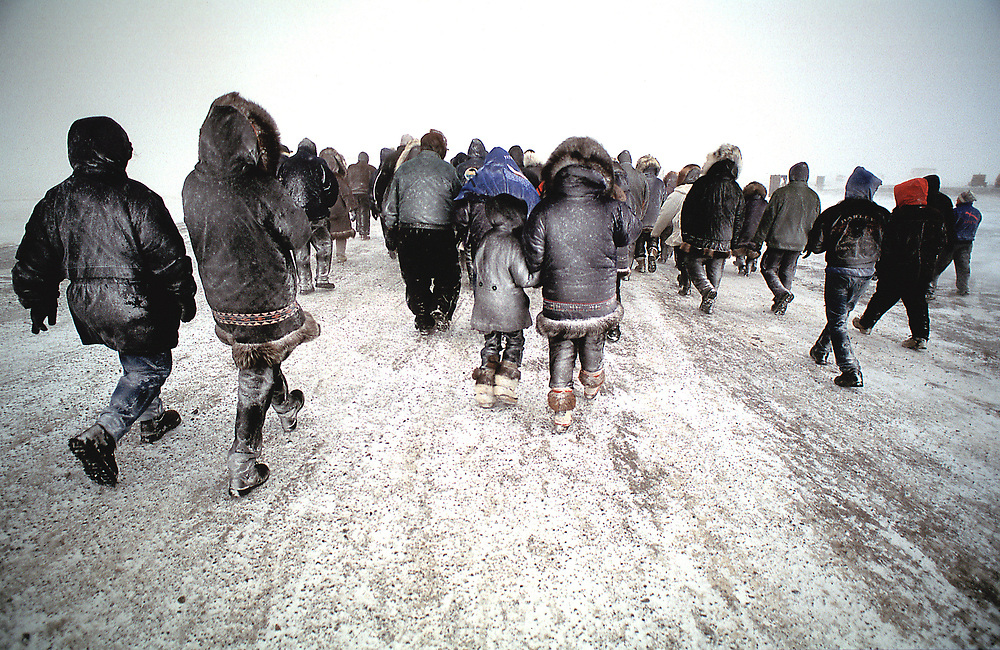 Alaska. Barrow. Community walking to graveyard for burial during 65 mile per hour winds.