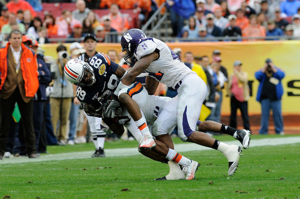 January 1, 2010: Wide receiver Darvin Adams of the Auburn Tigers is tackled by linebacker Quentin Davie of the Northwestern Wildcats during the NCAA football game between the Northwestern Wildcats and the Auburn Tigers in the Outback Bowl. The Tigers were leading the Wildcats 21-7 at halftime.