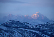 The last light of day sneaks past cloud cover and falls on the snowy steeps of the Tetons.
