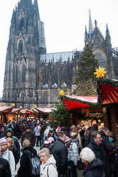 View of crowds and stalls in front of Cathedral at Christmas market in Cologne Germany