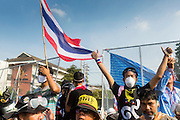 02 DECEMBER 2013 - BANGKOK, THAILAND: Anti-government protestors cheer after taking over a buffer zone between police and protestors Monday. Anti-government protestors and Thai police continued to face off Monday for a second day. Police used tear gas, water cannons and rubber bullets against protestors who charged their positions near the barriers on Chamai Maruchet bridge on Phitsanulok Road, which leads to the Government House.     PHOTO BY JACK KURTZ