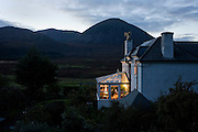 Barbara Christie, 58, sits alone in her conservatory at Swordale House overlooking Beinn Na Caillich (The Hill of the Old Woman) mountain. It is nearly dark at this northern latitude and it looks cosy inside this house with its warm and inviting lights. Barbara's father built this family home and she has lived in this house all her life apart from when studying in Edinburgh many years ago. It sits on a tiny road near Broadford on the Isle of Skye, beneath the magnificent hill whose myth goes back to a Norse Princess saga. Barbara sits in the more recent addition to the house, a conservatory that she enjoys sitting and reading away from her Summer Bed and Breakfast guests. Image taken for the 'UK at Home' book project published 2008.