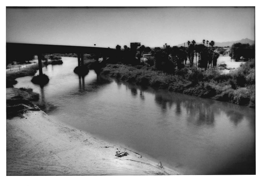 A young couple sunbathes on the banks of the greatly reduced Colorado just before it leaves the United States and enters Mexico.  The near bank is Yuma, Arizona, while the far bank is Winterhaven, California, USA.
