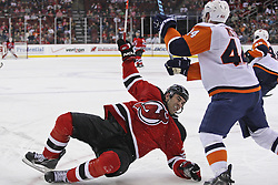 Apr 10, 2010; Newark, NJ, USA; New Jersey Devils right wing Pierre-Luc Letourneau-Leblond (22) takes a hit from New York Islanders defenseman Freddy Meyer (44) during the third period at the Prudential Center. The Devils defeated the Islanders 7-1.