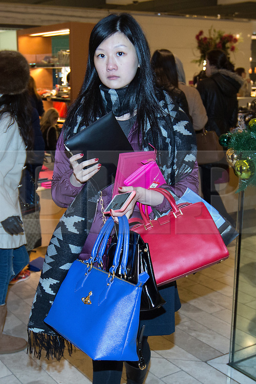 © Licensed to London News Pictures . 26/12/2014 .  Manchester , UK . A woman with numerous handbags on her arm in Selfridges in Manchester City Centre for the Boxing Day Sale . Photo credit : Joel Goodman/LNP