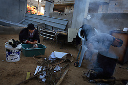 Subhia Al-Athamneh, 52, washes clothes early in the morning outside of her home, which was damaged after Israeli airstrikes targeting her neighbor went astray, Beit Hanoun, Gaza Strip, Palestinian Territories, Nov. 17, 2006. According to Human Rights Watch, since September 2005, Israel has fired about 15,000 rounds at Gaza while Palestinian militants have fired around 1,700 back.