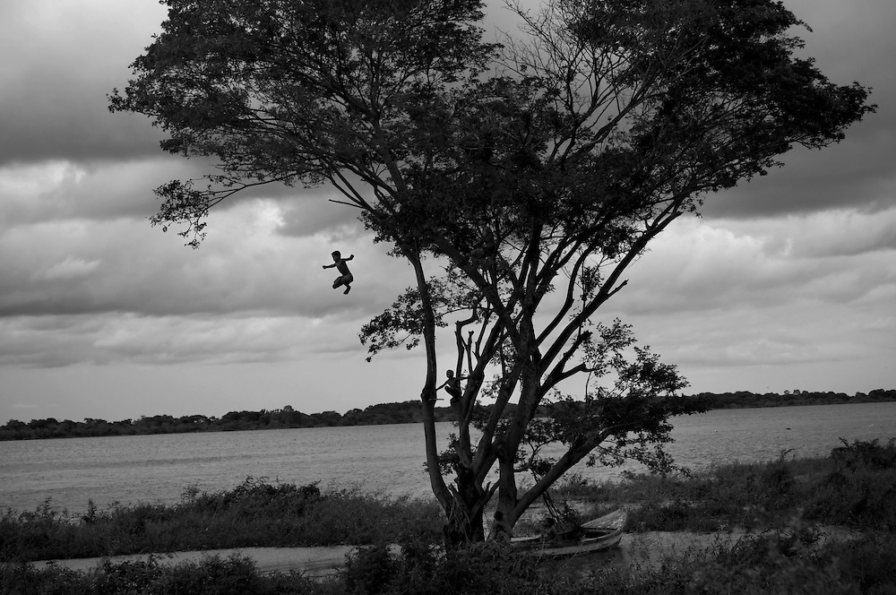 Warao boys play in the Orinoco river close to the camp where they live with other Warao indigenous persons, on the outskirts of the Cambalache garbage dump in Ciudad Guayana, in northeastern Venezuela. In an effort to escape poverty, hunger and to be closer to health care facilities, approximately 300 Warao indigenous persons from the Delta Amacuro have settled in Ciudad Guayana. The Warao sustain themselves and their families by salvaging recyclables, clothing and discarded food in Cambalache. Although Warao community leaders say their quality of life is improved in comparison to the conditions in the Delta, the Warao are still plagued by hunger and diseases consequential of the unsanitary conditions of living and working in Cambalache.