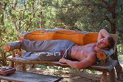 good looking shirtless man relaxing on a wooden bench outdoors