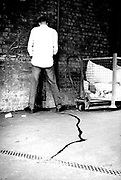 Man pissing against a wall UK 1990's.