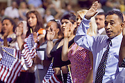 """04 JULY 2009 -- PHOENIX, AZ: Candidates for citizenship take the oath of citizenship and become US citizens at a naturalization ceremony in Phoenix, AZ.  U.S. Citizenship and Immigration Services and South Mountain Community College in Phoenix, AZ, hosted the 21st annual """"Fiesta of Independence"""" Saturday, July 4. More than 180 people from 58 countries took the US Oath of Citizenship and became naturalized US citizens. The ceremony was one of dozens of similar ceremonies held across the US this week. USCIS said more than 6,000 people were naturalized US citizens during the week.  Photo by Jack Kurtz / ZUMA Press"""