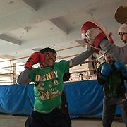 Jeunes garçons d' à peu près 9 années s'entraînent à côté du ring dans le gymnase du BBC. Les petits suivent le même programme d'entraînement des plus grands