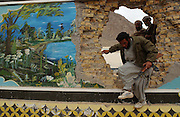 Anit-taliban fighters breaching the walled compound of Mullah Omar, the Taliban's spiritual leader in Kandahar. The walls were decorated with idyllic pastural scenes considered beautiful to the residents of this harsh desert terrain.