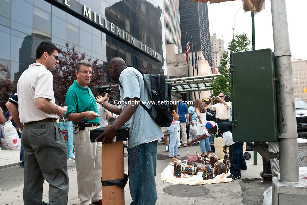 New York.  lower Manhattan. counterfeit luxury goods sellers in front of the world trade center after 9/11 . illegal immigrants, chinese, africans, senegalese  New York, Manhattan - United states  Vuiton, Gucci , Hermes, Prada / vendeur a la sauvette, de maroquinerie et objets de contrefacon devant le chantier du world trade center apres le 9 septembre; Manhattan, New York - Etats-unis Vuiton, Gucci , Hermes, Prada