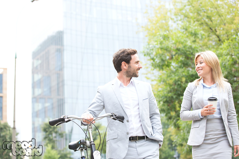 Businesspeople with bicycle and disposable cup conversing while walking outdoors
