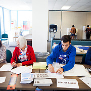 Poll workers assist voters at the University of California, San Diego on Tuesday.