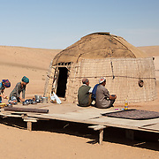 Young women prepare food outside a village home in the Karakum Desert, Turkmenistan