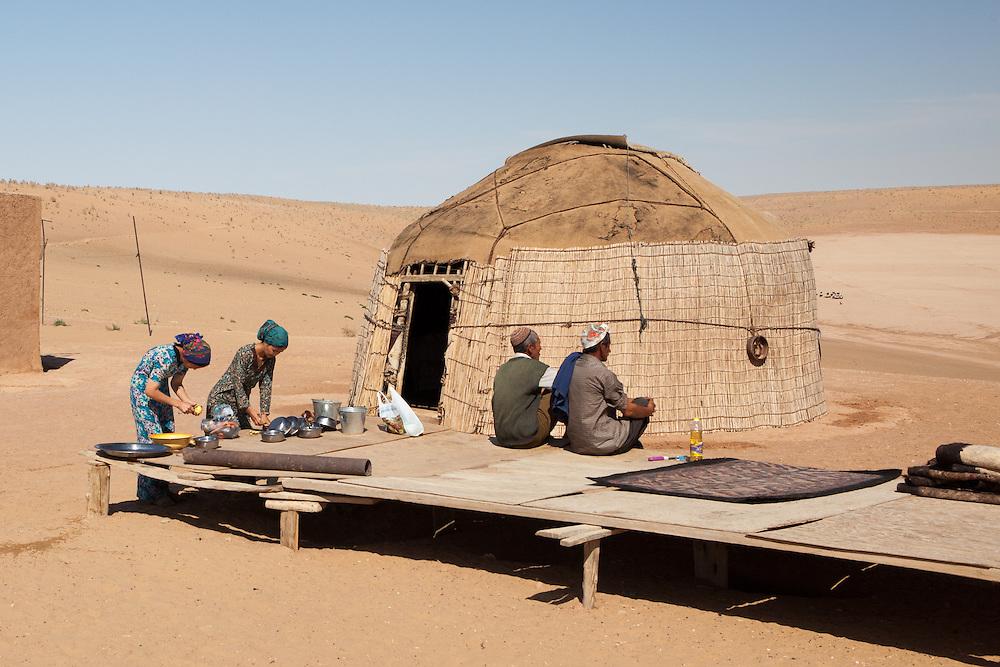Young women prepare food outside a village home in the Karakum Desert, Turkmenistan
