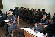 Boys studying during class at the Edhi Boys Home...In a country of some 160 million people, affordable education is beyond the reach of most parents in Pakistan. An education is considered a luxury to most people living in the slums of major cities and the rural areas of Pakistan. At an Edhi Boys Home some 56km outside Karachi 200 boys are offered a basic education and temporary home for up to 5 years. They are gain basic skills in literacy, numeracy,  English and Urdu. ..The facility provides a number of recreational facilities such as football and cricket as well as an on-site mosque. The facility relies solely on voluntary donations and is independent of government and commercial influence. ..The Edhi foundation was established by Abdul Sattar Edhi. Born in a small Indian own of Bantva in the province of Gujrat he migrated to Pakistan during partition in 1947. After working as a commissioning agent selling cloth in a market in Karachi Abdul Sattar Edhi and other members of his community decided to establish a free dispensary in the city. Disillusionment with the lack of health care led him to establish a welfare trust of his own called the Abdul Sattar Edhi Foundation. Appeals were made, funds raised and soon a home was established and a number of ambulances patrolled the streets of Karachi...In 1965 Adbul married a nurse working at the foundation, Bilquis. They have four children and all are involved in the current day to day running of the foundation. Bilquis Edhi runs a maternity home at the headquarters in Karachi and organises the adoption of illegitimate children and abandoned babies. The family share the foundation's vision of a single minded devotion to the cause of alleviation of human sufferings and a sense of personal responsibility. The foundation responds for calls of help from ordinary people, regardless of race, creed or status and now provides a priceless welfare service to the people of Pakistan...The foundation currently operates a fleet of 1200