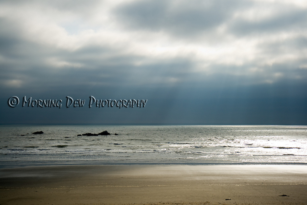 Evening sun streams through a heavy cloud cover at Kalaloch Beach. Olympic National Park, WA
