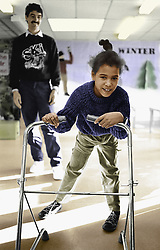 Young girl with disability using walking frame,